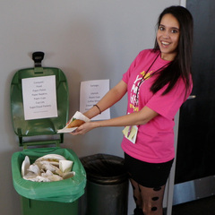 Young woman smiling at camera and placing paper item into open compost collection bin.