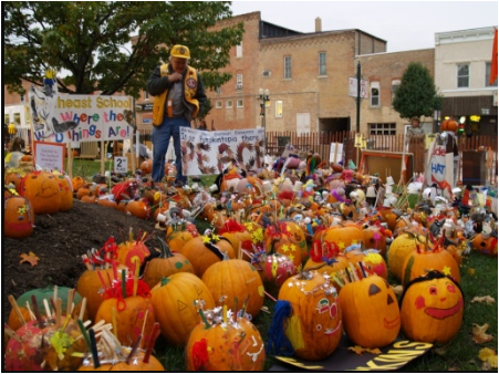 A man in a city square or common area looks at a large number of Jack-o-lanterns, most of which are brightly painted.
