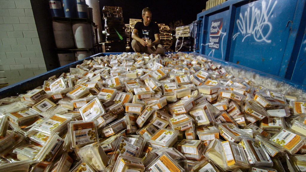 Squatting man looks at a large dumpster filled to the brim with packages of hummus.
