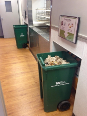 Waste Management bins in a hallway with signage on the wall above them.