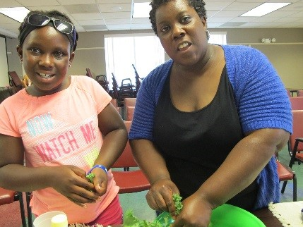 Two females smiling at camera in a conference room.  They appear to be working on a salad, tearing up greens. One is a child and the other is an adult; they may be a mother and daughter.