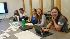 Multiple young people sitting at a conference table with laptops, papers and other items on table in front of them. They are clearly working, and smiling at camera.