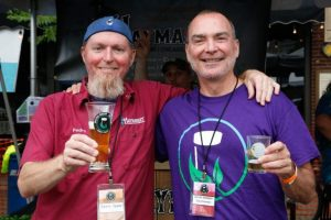 Gary Cuneen and another man stand with arms around each others shoulders, holding beers and smiling
