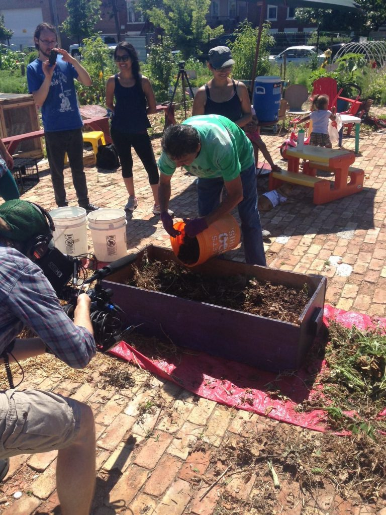 Several people standing outside around a raised garden bed in the center of view. A man is bent over the bed pouring in compost or soil from a bucket.