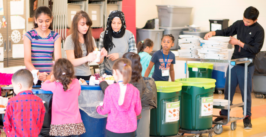 Image of multiple children in a classroom being lead through sorting food service wastes into recycling and compost bins.