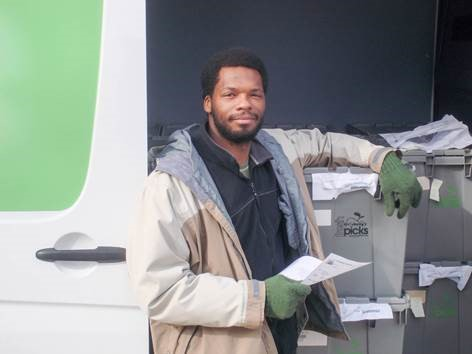 Worker smiling at camera with paperwork in hand, standing near delivery truck next to labelled packages.