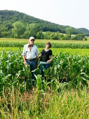 Man and woman standing a corn field with trees and hill in background