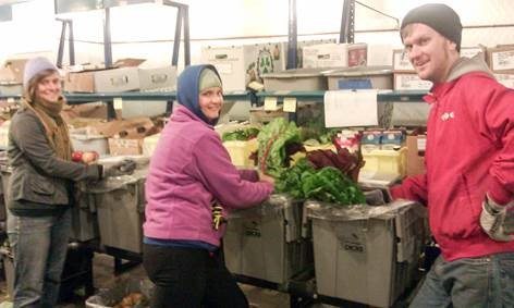 """A group of warehouse packers sorting through produce that will either be sent to customers or deemed """"Take Home"""" or """"Compost."""""""