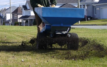 Person pushing a top dresser (wheeled machine casting compost from the bottom of a a bin shaped like an inverted pyramid) over a lawn. A street and houses are visible in the background.