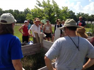 people standing around a compost bin during workshop