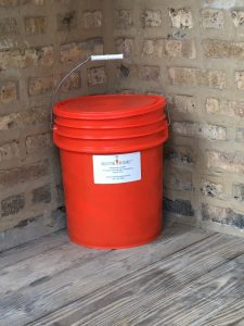 Orange handled bucket labeled as a Collective Resource Compost branded collection bin